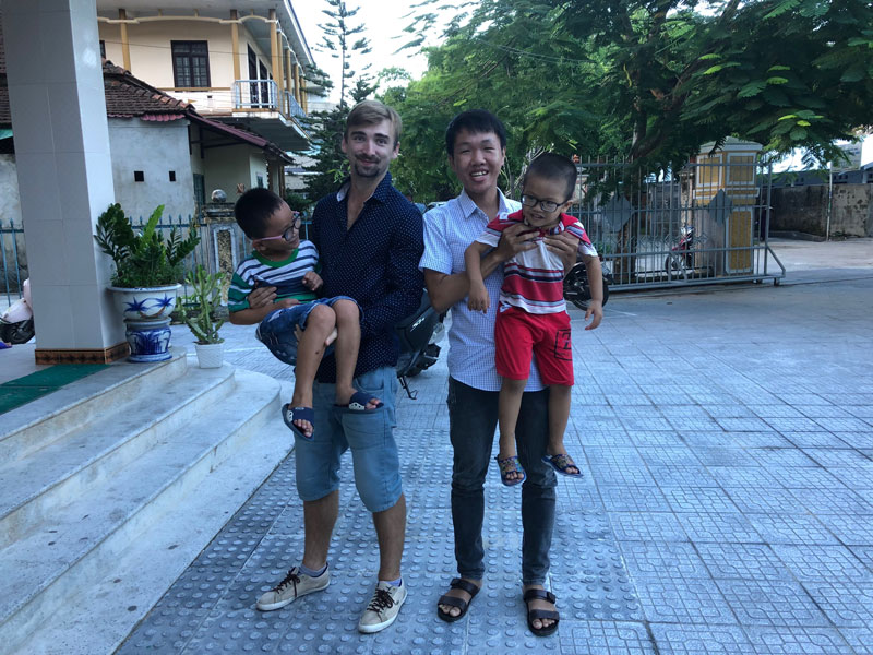 Lubomir Novohradsky and Bảo Phước are holding Blind kids