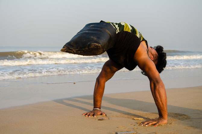 Mumbai beach and disable person who does not have two legs and he is able to manage handstand