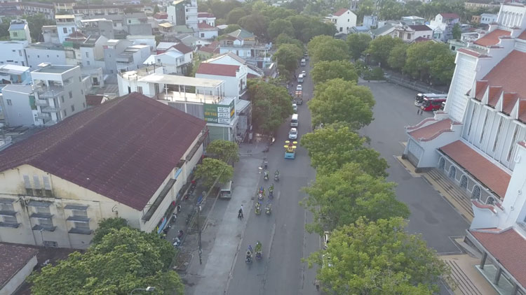 Picture from the drone where you can see Vietnamese Cyclo drivers are carrying flowers. Behind them, there is a car with a coffin.