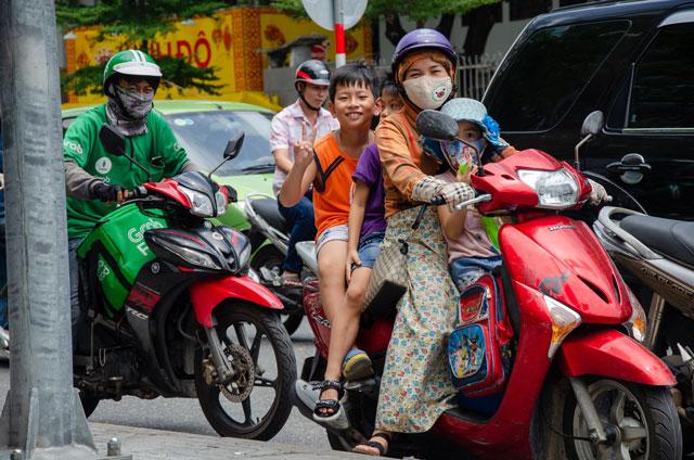 Three Vietnamese kids and his mom, are sitting on motorbike.