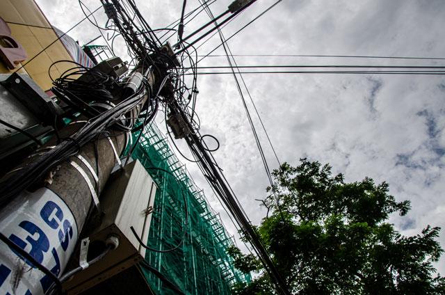 Sloup elektrického vedení obtočen kabely, za nímž se vypíná budova ve výstavbě. Výjev z města Danang.