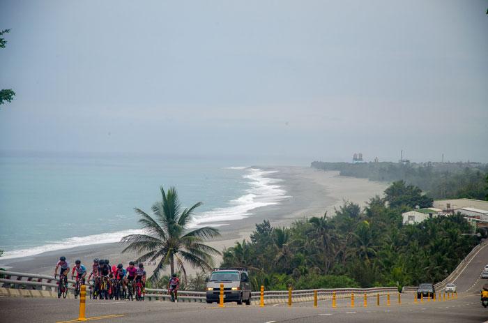 Nádherné pobřeží v pozadí při právě probíhajícím odlivu. Na silnici u pobřeží skupina cyklistů právě bojuje s převýšením.