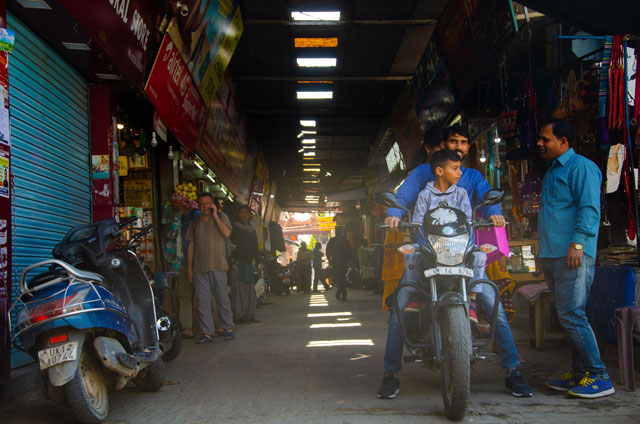 An busy alley covered by roof where you can see a father with her son on motorbike. It's close to the gate of Parmath Nikethan.