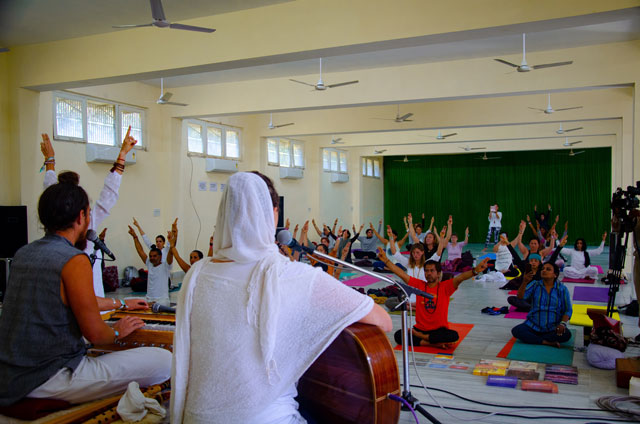 You can see students who are holding hands in the air and teachers who are playing on the guitar and harmonica. Yoga class combined with music.