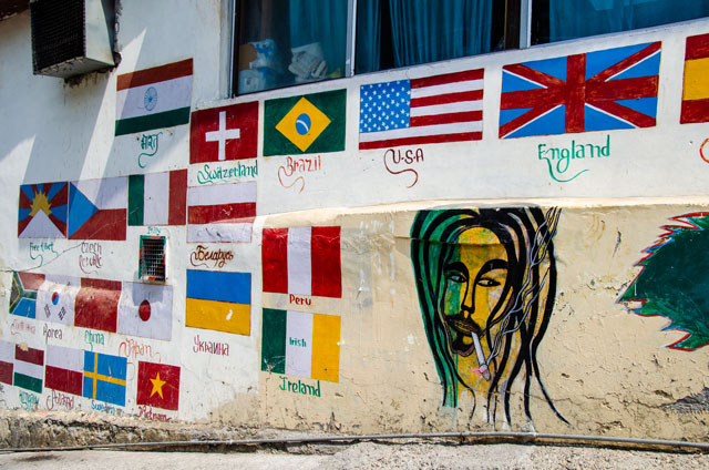 Many international flags are painted on the wall. You can see also Bob Marley, who is smoking joint.