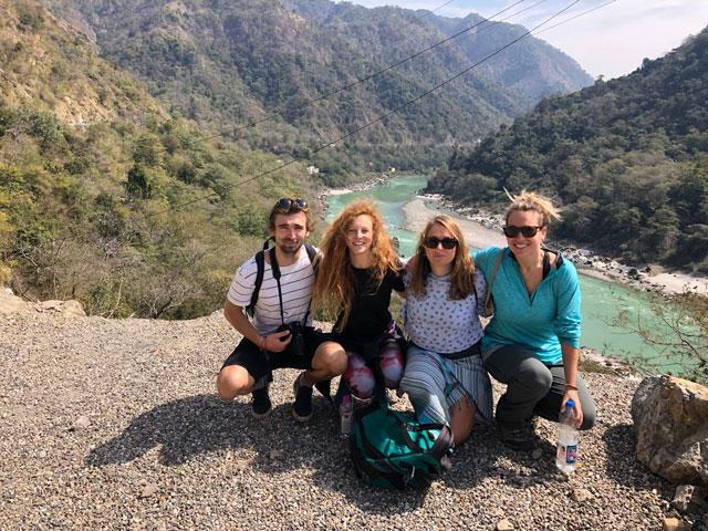 Čtyři lidé. za nimiž se táhne řeka Ganga, pózují pro fotografa.