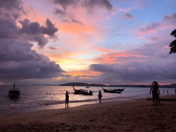Západ slunce v Thajsku, na Krabi ostrovech. Spolu s krásným odlivem, kde jsou na moři dvě loďky a pár lidí na pláži