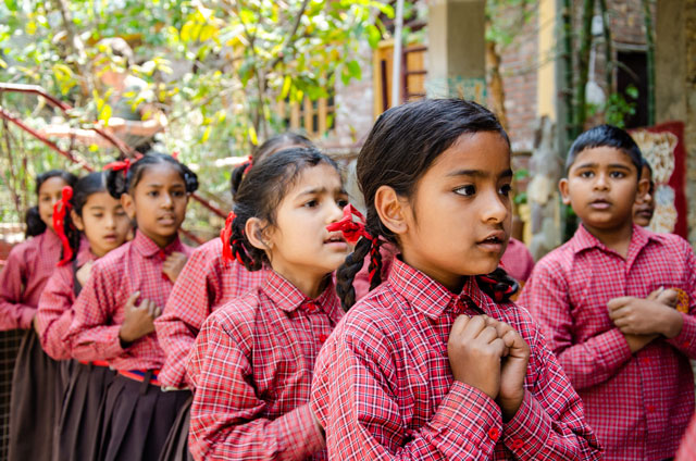 Kids are dancing and playing in the orphanage garden. They wear a red uniform.