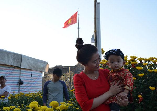 Vietnamka drží chlapečka, který je oblečený do Vietnamského kroje.