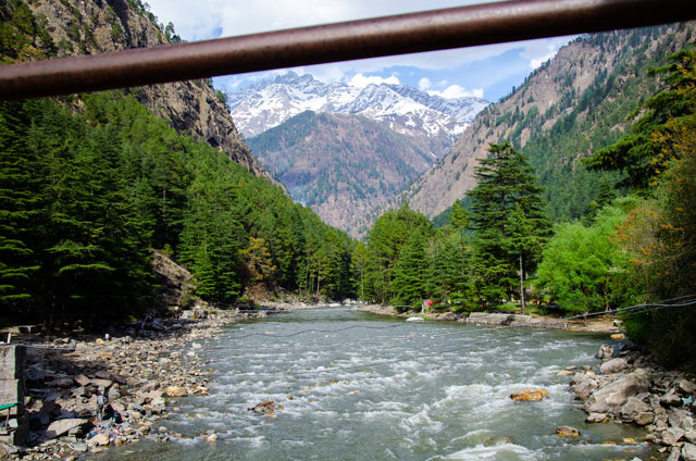 On the top, you can see a mountain covered by snow and in the middle green trees and on the bottom river. The picture was taken in Kasol.