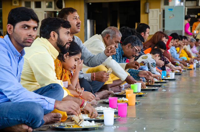 Indian people are eating on the ground with their hands.