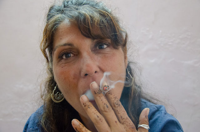 An woman in middle age is smoking a joint in Kasol.