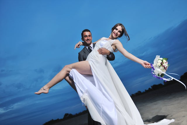 Bridegroom is holding his bride and posing for the wedding picture.
