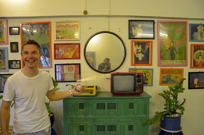 A traveller is showing the Airbnb apartment in Hanoi City. Old Vietnamese furniture and an old tv with many pictures on the wall around.